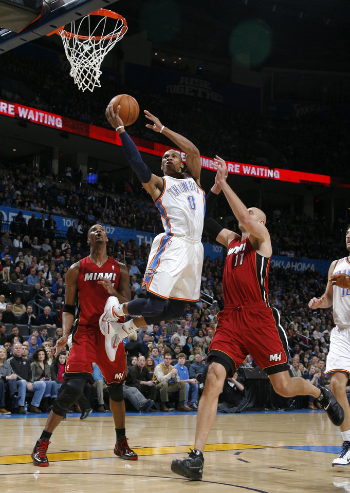 Photo - Oklahoma City's Russell Westbrook (0) shoots in between Miami's Chris Bosh (1) and Miami's Zydrunas Ilgauskas (11)during the NBA basketball game between Oklahoma City and Miami at the OKC Arena in Oklahoma City, Thursday, Jan. 30, 2011. Photo by Sarah Phipps, The Oklahoman