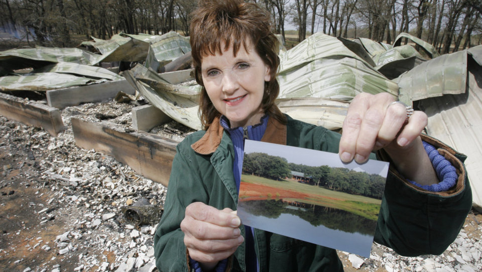 Photo - FIRES / WILDFIRES / DAMAGE/ AFTERMATH / RETURN: Jammy England holds up a photo of Cory's Cabin before it was destroyed in Thursday's fires north of Lindsay, Friday, April 10, 2009. Cory's Cabin was built to honor her son who died of cancer and was used as a church retreat and wedding were held there.   Photo By David McDaniel, The Oklahoman. ORG XMIT: KOD