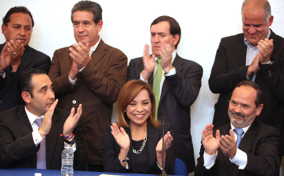 Photo -   FILE - In this April 9, 2012 file photo, Josefina Vazquez Mota, presidential candidate for the ruling National Action Party, PAN, bottom center, applauds during a news conference with top members of her party in Mexico City. Bottom row at left is Roberto Gil and bottom row at right is Gutavo Madero. Top row from left to right is Max Cortazar, Diodoro Carrasco, Rafael Gimenez and Juan Ignacio Zavala. Vazquez Mota exulted in the explosion of camera flashes as a pumped-up crowd cheered her victory in a bruising three-way race to become the presidential candidate of Mexico's ruling party. With her daughters behind her, the candidate pledged to become Mexico's first female president. Within weeks she was within single digits of the frontrunner in the July 1 election. (AP Photo/Alexandre Meneghini, file)