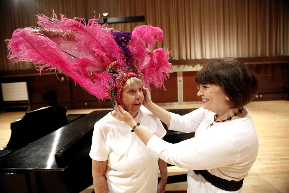 Former Senior Follies cast member Katherine Schlageter, right, helps fit Betty Windsor with a head piece made by costume designer Ashley Bellet.  Photo by Sarah Phipps, The Oklahoman Archives