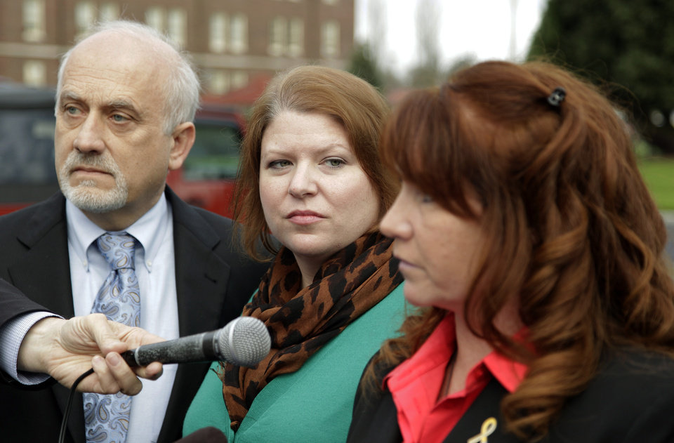 Photo -   Kari Bales, center, stands next to attorney Lance Rosen, left, as they listen as her sister, Stephanie Tandberg, right, reads a statement to reporters Tuesday, Nov. 13, 2012, outside the building housing a military courtroom on Joint Base Lewis McChord in Washington state, where a preliminary hearing ended Tuesday for Kari's husband, U.S. Army Staff Sgt. Robert Bales. Bales is accused of 16 counts of premeditated murder and six counts of attempted murder for a pre-dawn attack on two villages in Kandahar Province in Afghanistan in March of 2012. (AP Photo/Ted S. Warren)