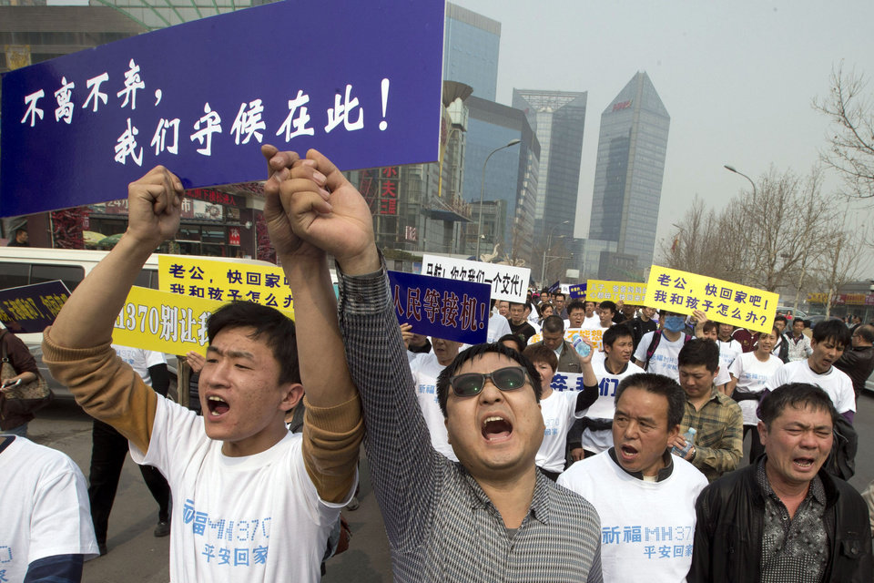 Photo - FILE - In this Tuesday, March 25, 2014 file photo, Chinese relatives of passengers onboard the missing Malaysia Airlines plane, flight MH370, shout in protest as they march towards the Malaysia embassy in Beijing, China. Authorities have been forced on the defensive by the criticism, the most forceful of which has come from a group of Chinese relatives who accuse them of lying about - or even involvement in - the disappearance of Flight 370. The blue placard reads: