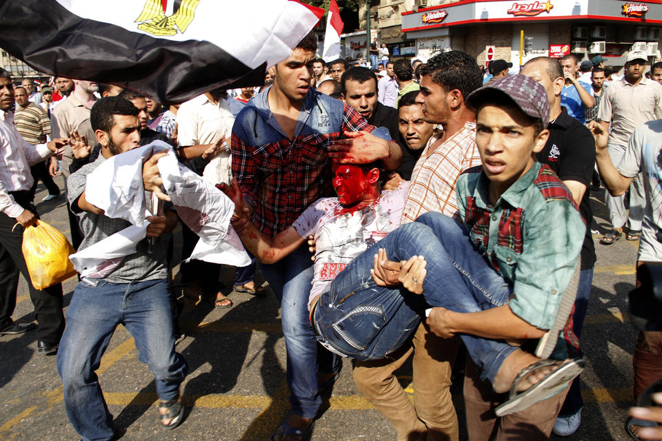 A wounded Egyptian protester is carried away from the site of clashes in Tahrir Square in Cairo, Egypt, Friday, Oct. 12, 2012. Supporters of Egypt�s new Islamist president stormed a stage erected by opposition activists, smashed loudspeakers and tore the structure down during competing protests Friday in Cairo. The scuffles between supporters and opponents of President Mohammed Morsi reflect deep political divisions among the country�s 82 million people, more than a year after the popular uprising that toppled Hosni Mubarak. (AP Photo/Mostafa el-Shemy)