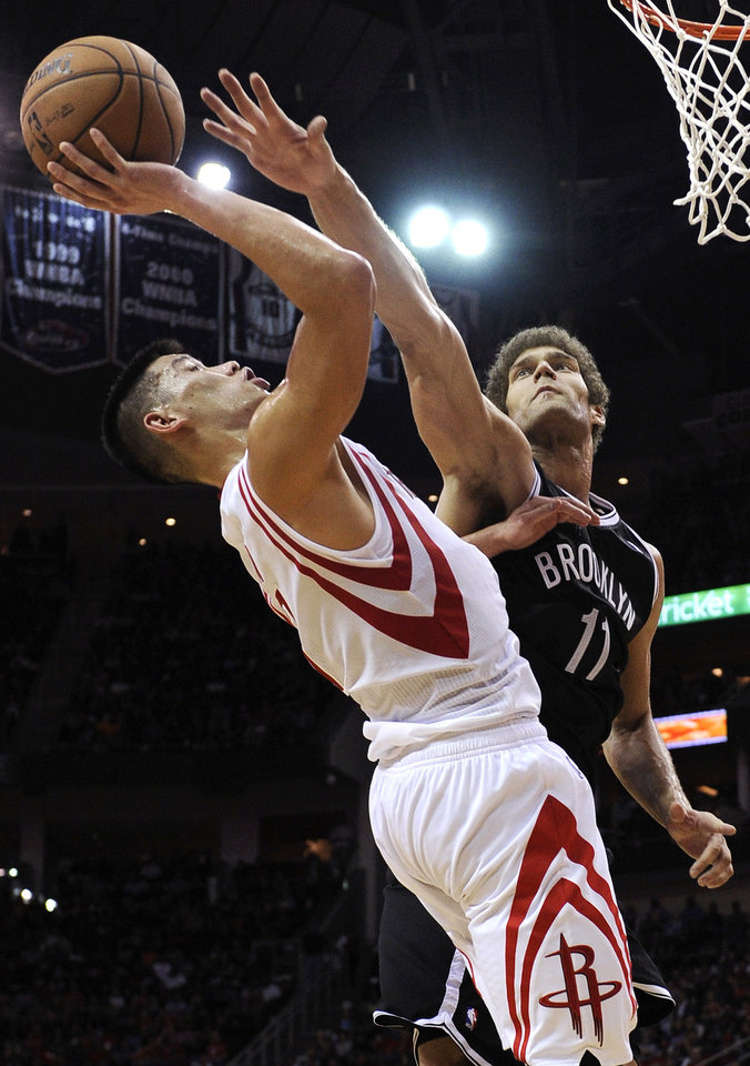 Photo - Houston Rockets' Jeremy Lin (7) tries to shoot over Brooklyn Nets' Brook Lopez (11) in the second half of an NBA basketball game Saturday, Jan. 26, 2013, in Houston. The Rockets won 119-106. (AP Photo/Pat Sullivan)