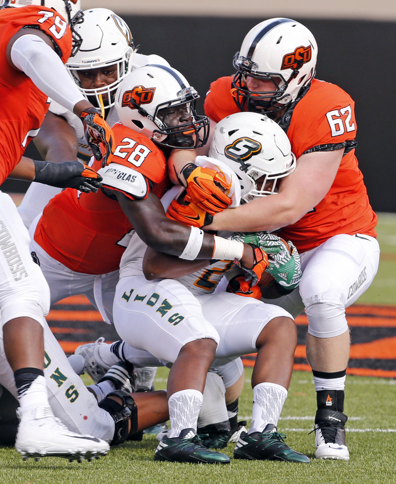 Photo - Kevin Henry (28) and Tyler Ferguson bring down Louisiana's Rasheed Harrell (2) and during the second half of a college football game between the Oklahoma State Cowboys (OSU) and the Southeastern Louisiana Lions at Boone Pickens Stadium in Stillwater, Okla., Saturday, Sept. 12, 2015. Photo by Steve Sisney, The Oklahoman