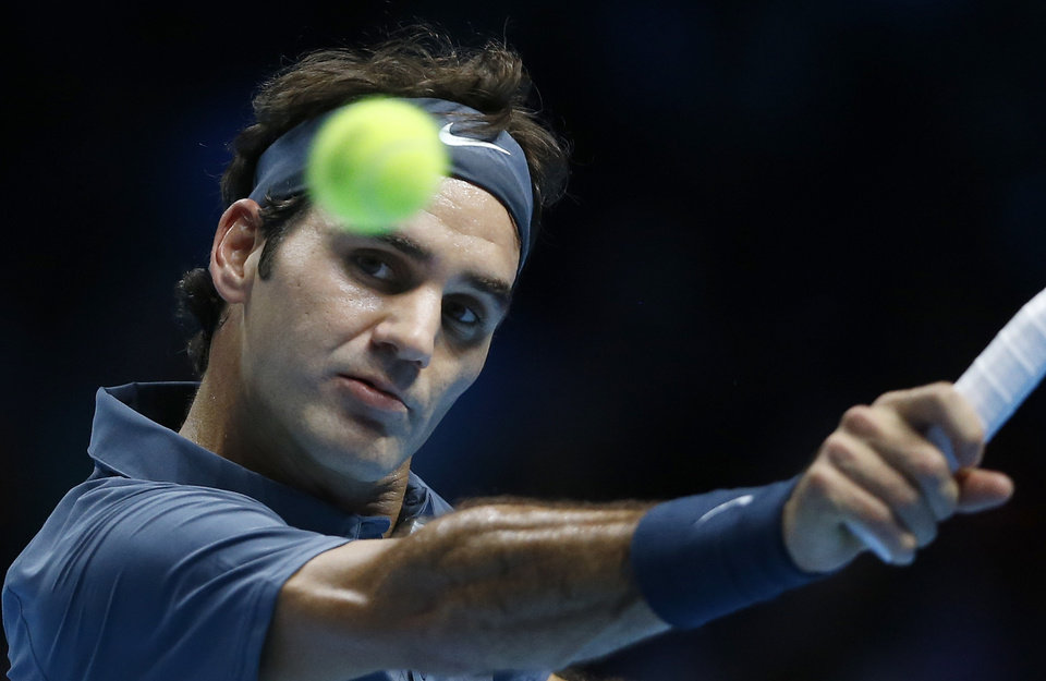 Photo - Roger Federer of Switzerland plays a return to Richard Gasquet of France during their ATP World Tour Finals tennis match at the O2 Arena in London, Thursday, Nov. 7, 2013. (AP Photo/Kirsty Wigglesworth)