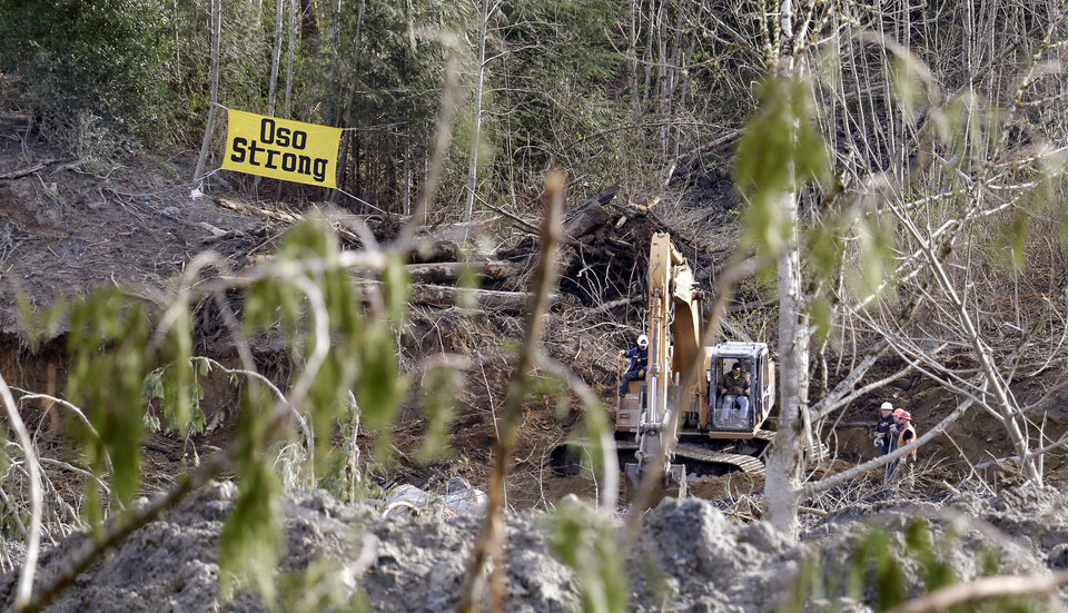 Photo - Searchers work with heavy equipment near the edge of a deadly mudslide, Wednesday, April 2, 2014, in Oso, Wash. Officials have so far confirmed the deaths of 29 people, although only 22 have been officially identified in information released Wednesday morning by the Snohomish County medical examiner's office. (AP Photo/Elaine Thompson)