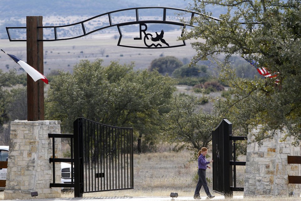 Photo - An employee opens the gate to let out cars at the entrance Rough Creek Lodge, Sunday, Feb. 3, 2013. Chris Kyle and Chad Littlefield were found murdered at the gun range on the property. (AP Photo/The Fort Worth Star-Telegram, Richard W. Rodriguez)