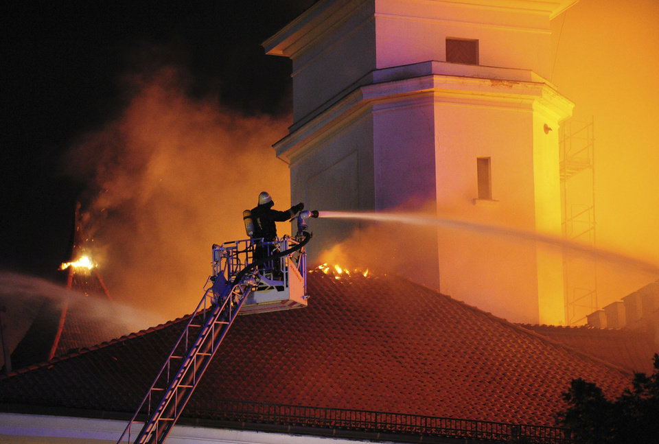Photo - In this photo released by China's Xinhua Agency, a firefighter tries to extinguish blaze on the roof of Riga Castle, Latvia, Thursday, June 20, 2013. The Baltic News Service is reporting that a fire has partially damaged the Riga Castle, a medieval fortress that houses the National History Museum of Latvia. The castle normally serves as the presidential residence, but BNS says Latvian President Andris Berzins is staying elsewhere as the building is being renovated. (AP Photo/Xinhua, Guo Qun) NO SALES