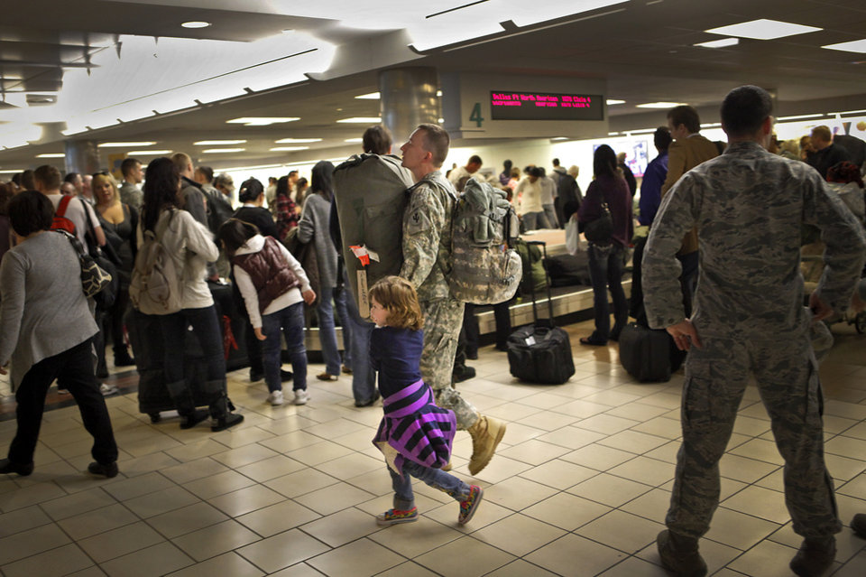 Master Sgt. Daryl Schonfarber walks with his daughter Julia, 5, through the baggage claim as troops from the Third Combat Communications Group of Tinker Air Force Base arrive at Will Rogers World Airpot from a six month deployment in Afghanistan on Thursday, Jan. 6, 2011, in Oklahoma City, Okla. Photo by Chris Landsberger, The Oklahoman