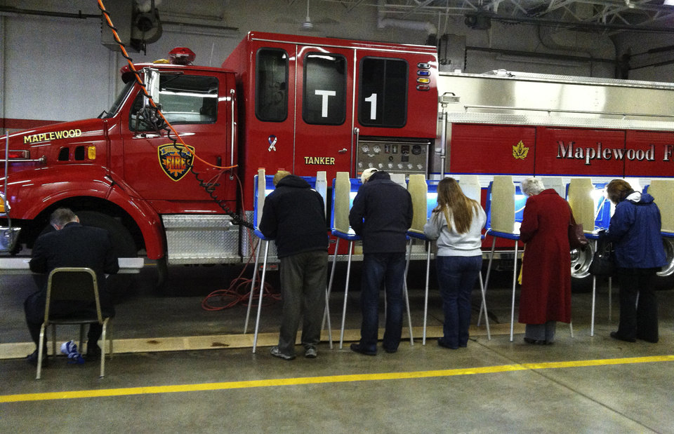 Voters cast their ballots on Election Day, Tuesday, Nov. 6, 2012, next to a fire engine at Maplewood Fire Station No. 4 in Maplewood, Minn. (AP Photo/The Star Tribune, Richard Sennott) MANDATORY CREDIT; ST. PAUL PIONEER PRESS OUT; MAGS OUT; TWIN CITIES TV OUT