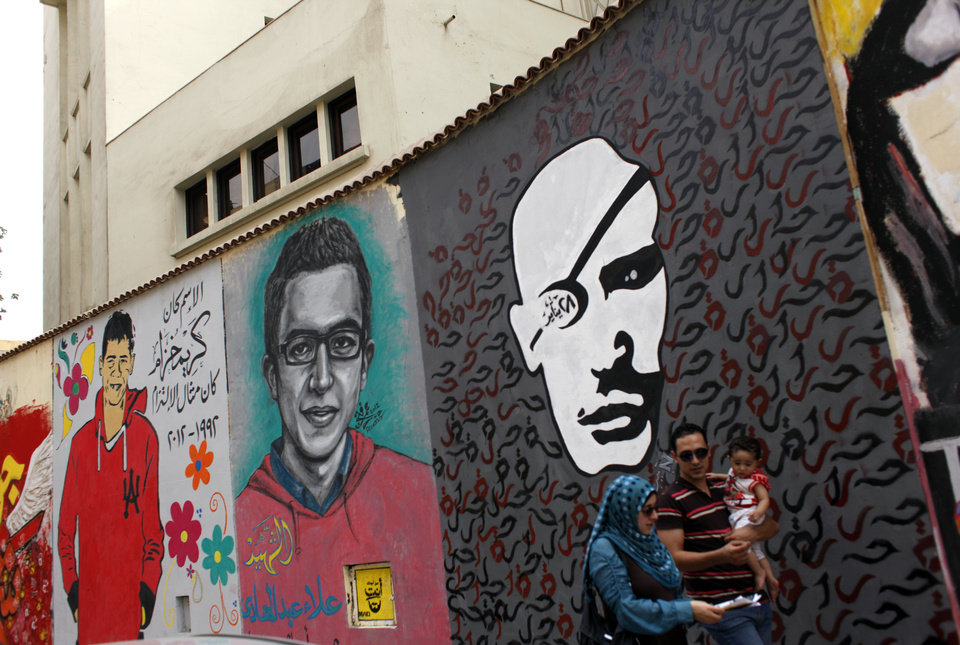 "In this Thursday, Oct. 4, 2012 photo, an Egyptian family walks past murals with Arabic that reads, ""his name was Karim Khozam, he was a symbol of commitment, 1992-2012,"" in Tahrir square, Cairo, Egypt. Graffiti has been among the most powerful art forms and tools of Egypt's revolution and the turbulent months since, but it also has proven to be its most vulnerable and ephemeral. So a group of artists, photographers and a publisher joined hands to preserve the images. ""Wall Talk"" _ their newly released, 680-page book _ collects hundreds of photos of graffiti dating from the Jan. 25, 2011 eruption of the revolt against then-President Hosni Mubarak until today. (AP Photo/Nasser Nasser)"