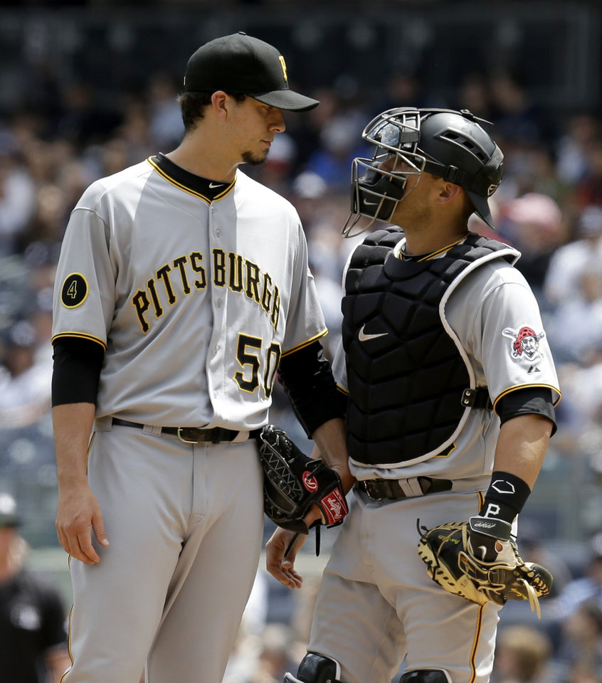Photo - Pittsburgh Pirates starting pitcher Charlie Morton, left, talks with catcher Tony Sanchez after giving up two runs during the first inning of the first baseball game of a double-header against the New York Yankees at Yankee Stadium, Sunday, May 18, 2014 in New York. (AP Photo/Seth Wenig)