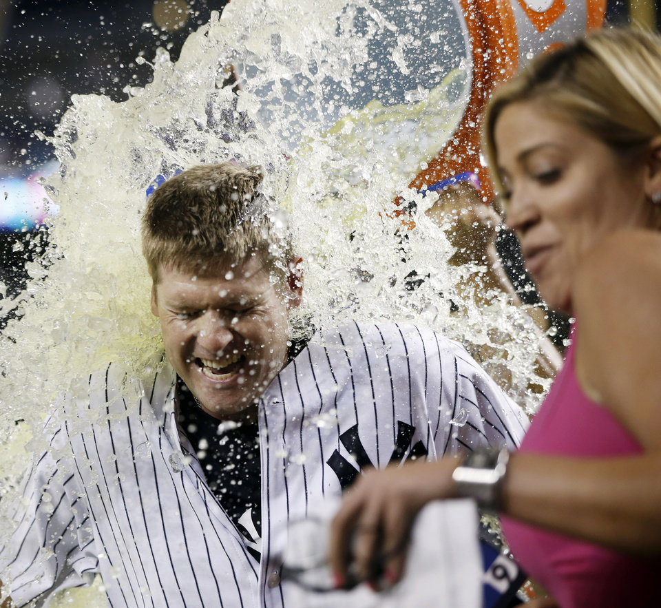 Photo - New York Yankees Chase Headley reacts as he is doused with Gatorade after hitting a game-winning, 14th-inning, walk-off RBI single in the Yankees 2-1 victory over the Texas Rangers in a baseball game at Yankee Stadium in New York, Wednesday, July 23, 2014. YES Network announcer Meredith Marakovits backs away, right. (AP Photo)