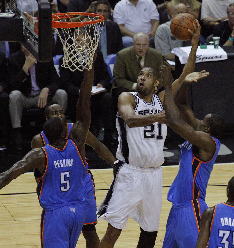 Photo - San Antonio's Tim Duncan (21) goes to the basket between Oklahoma City's Kendrick Perkins (5), James Harden (13), and Serge Ibaka (9) during Game 2 of the Western Conference Finals between the Oklahoma City Thunder and the San Antonio Spurs in the NBA playoffs at the AT&T Center in San Antonio, Texas, Tuesday, May 29, 2012. Oklahoma City lost 120-111. Photo by Bryan Terry, The Oklahoman