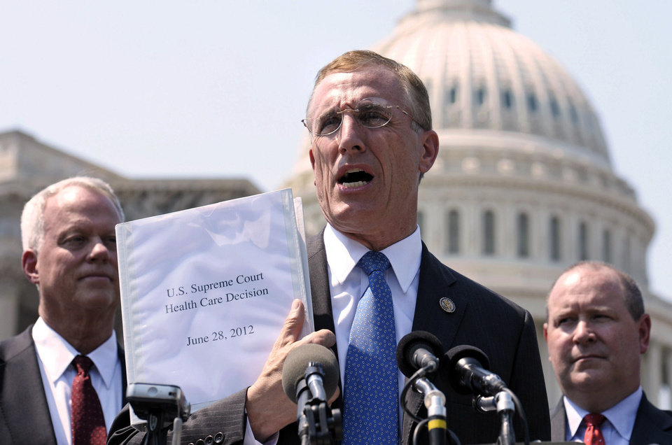 FILE - In this Thursday, June 28, 2012 file photo, Rep. Tim Murphy, R-Pa., center, holds up a copy of the Supreme Court's health care ruling during a news conference by the GOP Doctors Caucus on Capitol Hill in Washington. The Supreme Court caught many by surprise when it backed the Obama administrationís health care reform in June 2012. The law requires Americans to buy insurance or pay a tax, while subsidizing the needy. (AP Photo/Cliff Owen, File)
