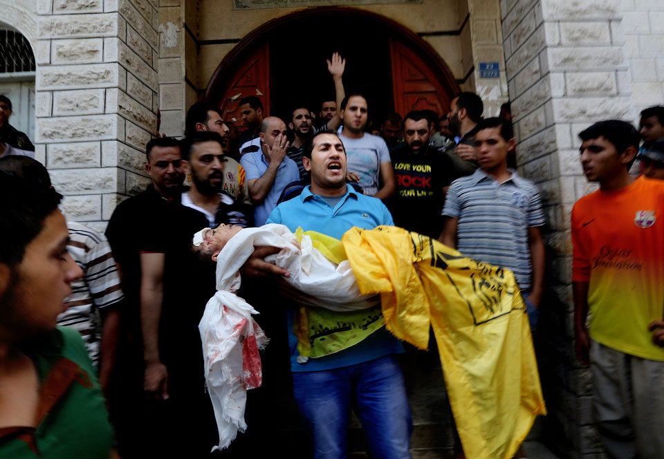 Photo - Palestinians carry the lifeless bodies of Qasim Alwan, 4, Imad Alwan, 6, who were killed Friday by an Israeli tank shell, during their funeral in Gaza City, Saturday, July 19, 2014. Relatives say the tank shell kit the Alwan family's kitchen, killing Qasim and Imad. (AP Photo/Hatem Moussa)