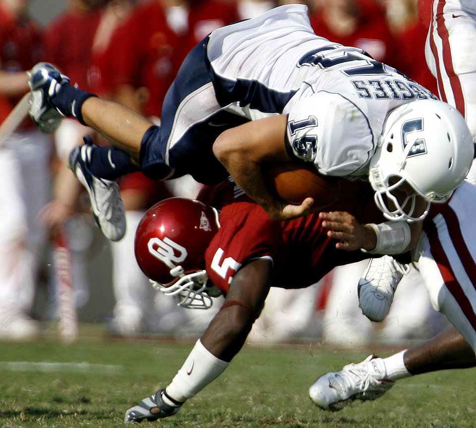 Photo - Nic Harris of OU tackles Jase McCormick of Utah State University during the second half of the University of Oklahoma Sooners (OU) college football game against Utah State at the Gaylord Family -- Oklahoma Memorial Stadium, on Saturday, Sept. 15, 2007, in Norman, Okla.  By Bryan Terry, The Oklahoman     ORG XMIT: KOD