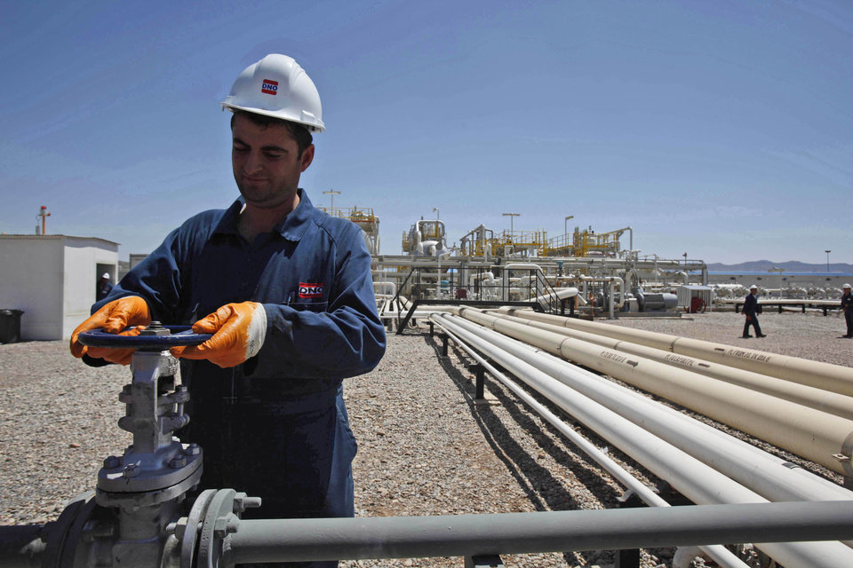 Photo - FILE - In this May 31, 2009 file photo, an employee works at the Tawke oil fields in the semiautonomous Kurdish region in northern Iraq. An Iraqi Kurdish official says the country's self-ruled northern Kurdish region has suspended oil exports over a payment row with the central government in Baghdad. (AP Photo/Hadi Mizban, File)