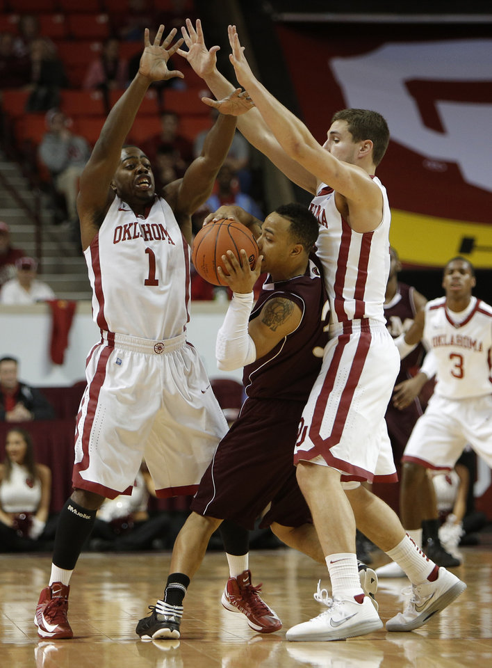 Oklahoma's Sam Grooms (1) and Tyler Neal (15) guard Louisiana's Marcelis Hansberry (3) during a men's college basketball game between the University of Oklahoma and the University of Louisiana-Monroe at the Loyd Noble Center in Norman, Okla., Sunday, Nov. 11, 2012.  Photo by Garett Fisbeck, The Oklahoman
