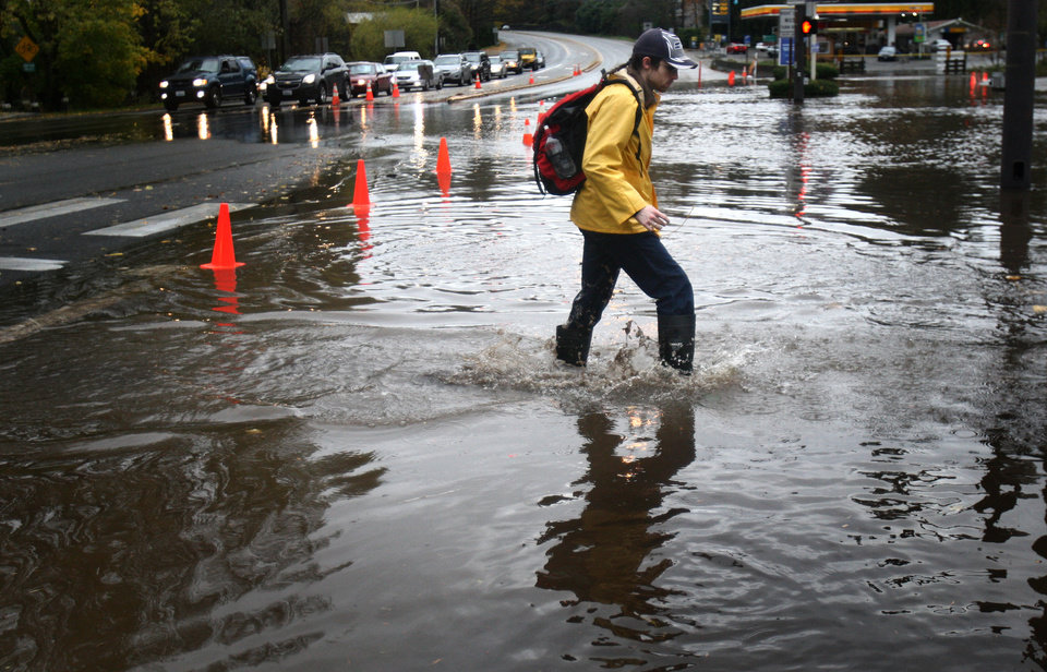 Photo -   A pedestrian makes his way across a flooded section of Bothell Way NE in Lake Forest Park in Seattle, during a significant rainfall on Monday, Nov. 19, 2012. Residents in Washington and Oregon are bracing for expected river flooding after heavy rain and winds that caused sporadic road closures, power outages and at least one death. The wet weather is expected to continue throughout the week, after hurricane-strength winds battered both states along the coast. (AP Photo/seattlepi.com, Joshua Trujillo)