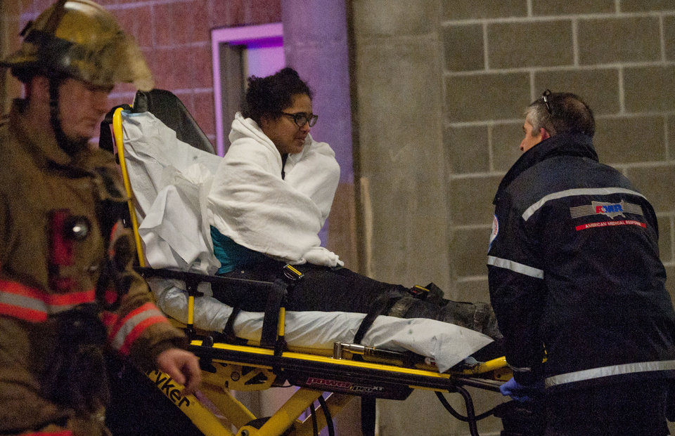A woman who was trapped inside a wall of the parking garage is taken to an ambulance, Wednesday, Jan. 16, 2013 in Portland, Ore. Firefighters cut a hole through concrete and used an air bag and a soapy lubricant to free the woman. The woman spent about four hours in a space 8 to 10 inches wide before rescuers managed to free her as television cameras filmed much of the effort. Firefighters said they hadn\'t gotten a clear explanation of the woman\'s predicament. Lt. Rich Chatman of the Portland fire department, said she had been seen smoking or walking on the roof of a two-story building before she fell. (AP Photo/The Oregonian, Brent Wojahn) MAGS OUT; TV OUT; LOCAL TV OUT; LOCAL INTERNET OUT; THE MERCURY OUT; WILLAMETTE WEEK OUT; PAMPLIN MEDIA GROUP OUT
