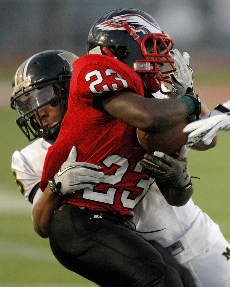 Del City's Anthony Mason is brought down by Midwest City's Zeke Lewis during a high school football game in Del City, Okla., Friday, September 2, 2011. Photo by Bryan Terry, The Oklahoman