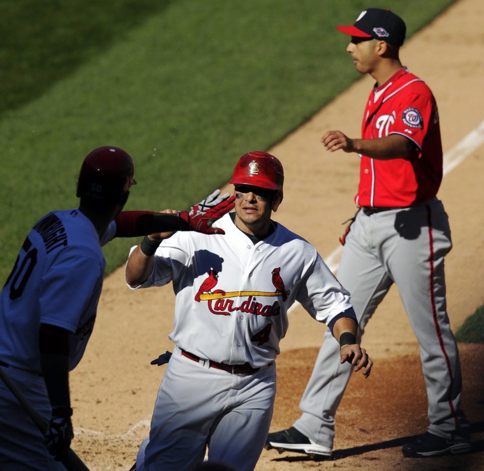 St. Louis Cardinals' Yadier Molina, center is congratulated by Adam Wainwright after scoring on a wild pitch by Washington Nationals starting pitcher Gio Gonzalez, top right, during the second inning in Game 1 of baseball's National League division series, Sunday, Oct. 7, 2012, in St. Louis. (AP Photo/Tom Gannam)