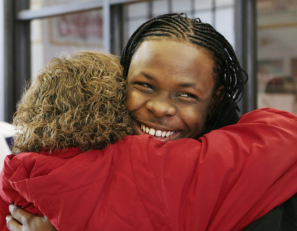 Photo - Carl Albert High School defensive back Daytawion Lowe smiles as he is hugged by a woman after the ceremony where he signed a letter of intent  in the school's athletic facility to play football at Oklahoma State University Wednesday afternoon, February 4, 2009.  BY JIM BECKEL, THE OKLAHOMAN ORG XMIT: KOD