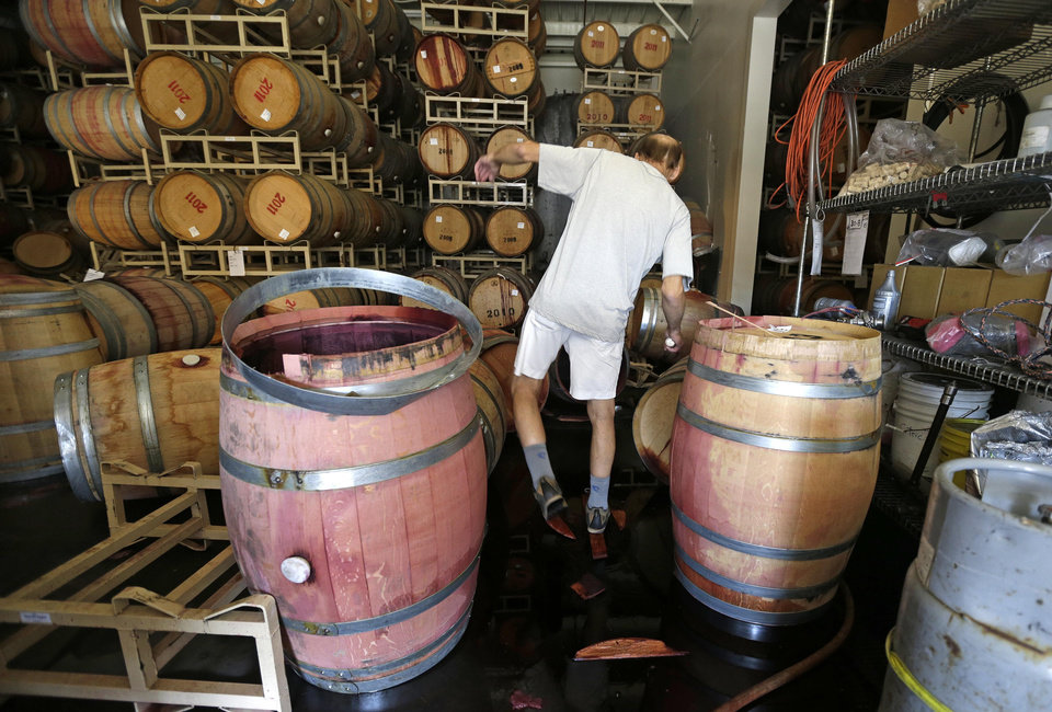 Photo - Winemaker Tom Montgomery walks through wine to see the damage following an earthquake at the B.R. Cohn Winery barrel storage facility Sunday, Aug. 24, 2014, in Napa, Calif. Winemakers in California's storied Napa Valley woke up to thousands of broken bottles, barrels and gallons of ruined wine as a result of Sunday's earthquake.  (AP Photo/Eric Risberg)