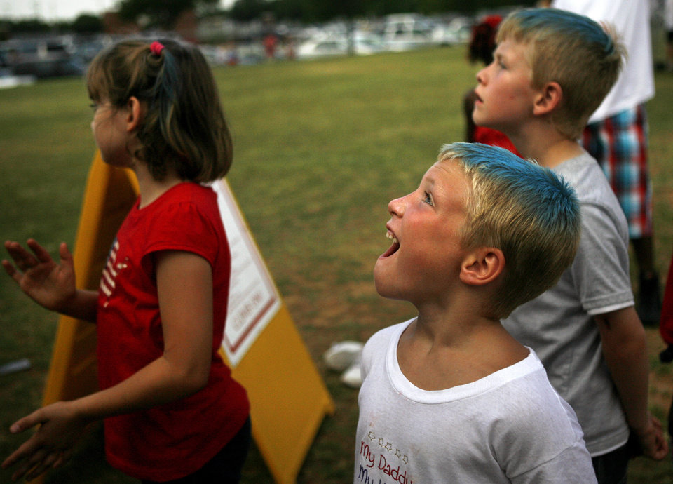 Jacob Kleinschmidt, 6, middle, watches kids at the rockclimbing wall while Cherokee Manken, 9, and Devan Jowers, 7, also wait in line Saturday, July 4, 2009 at UCO campus in Edmond, Okla. Photo by Ashley McKee, The Oklahoman