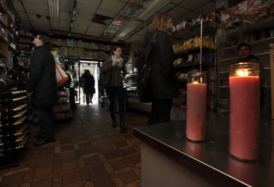 Photo -   People shop in a candle-lit deli in New York's Tribeca neighborhood, Wednesday, Oct. 31, 2012. In lower Manhattan, some stores are open even though their power is still out. Others are busing essential employees to work. Days after superstorm Sandy hit, businesses both big and small are facing a tough choice, to reopen or stay closed.(AP Photo/Richard Drew)