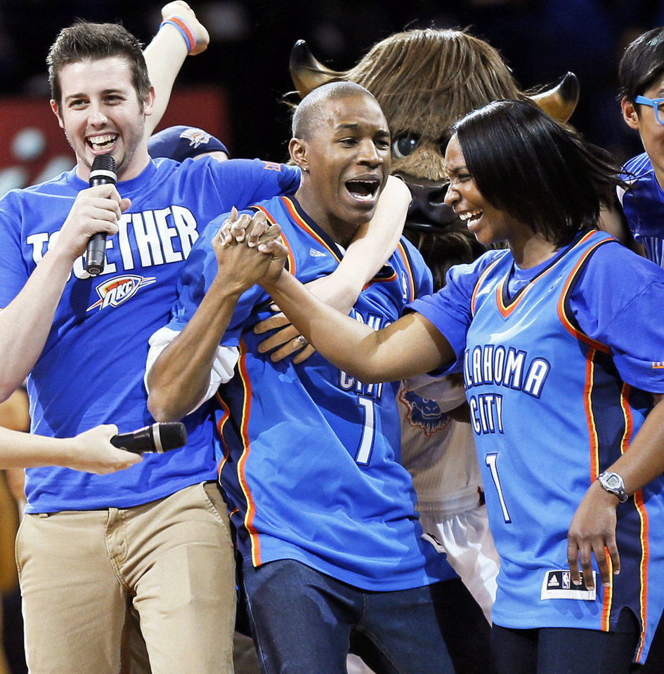 Photo - Larry Hill, middle, and his girlfriend, Niki Wright, react after Hill made the $20,000 half-court shot during Game 1 in the first round of the NBA playoffs between the Oklahoma City Thunder and the Houston Rockets at Chesapeake Energy Arena in Oklahoma City, Sunday, April 21, 2013. Oklahoma City won, 120-91. Photo by Nate Billings, The Oklahoman