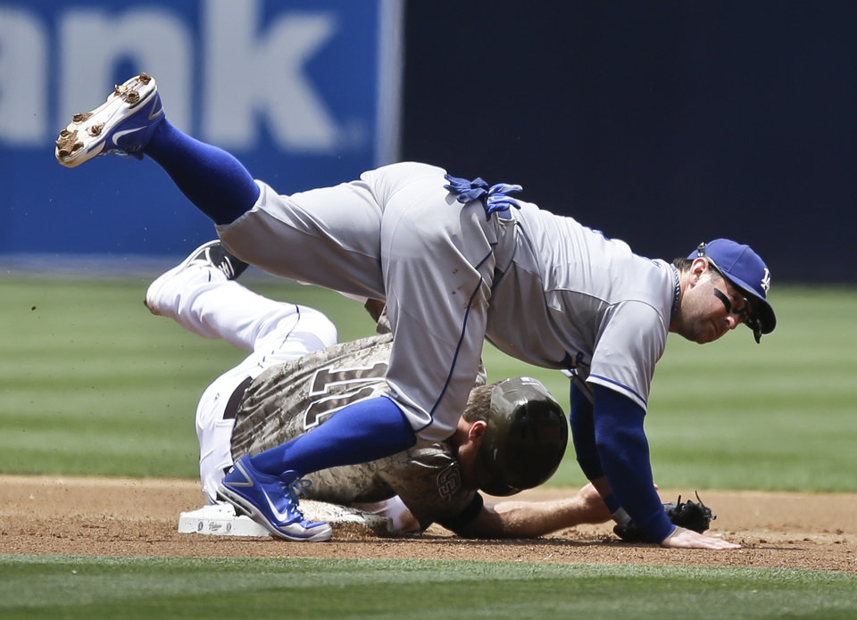 Photo - Los Angeles Dodgers second baseman Nick Punto tumbles over San Diego Padres' Logan Forsythe while relaying to first to complete a double play in the first inning of a baseball game in San Diego, Sunday, June 23, 2013. (AP Photo/Lenny Ignelzi)