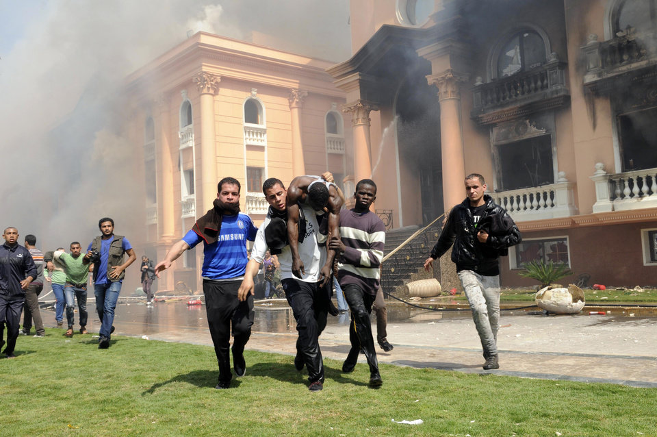 Photo - An injured security official is carried from a police officers club in the upscale neighborhood of Zamalek, after protesters set fires following a court verdict in Cairo, Egypt, Saturday, March 9, 2013. Fans of Cairo's Al-Ahly club have stormed Egypt's soccer federation headquarters and a nearby police club, and set them ablaze after a court acquitted seven of nine police official on trial for their alleged part in deadly stadium melee. (AP Photo/Mohammed Asad )