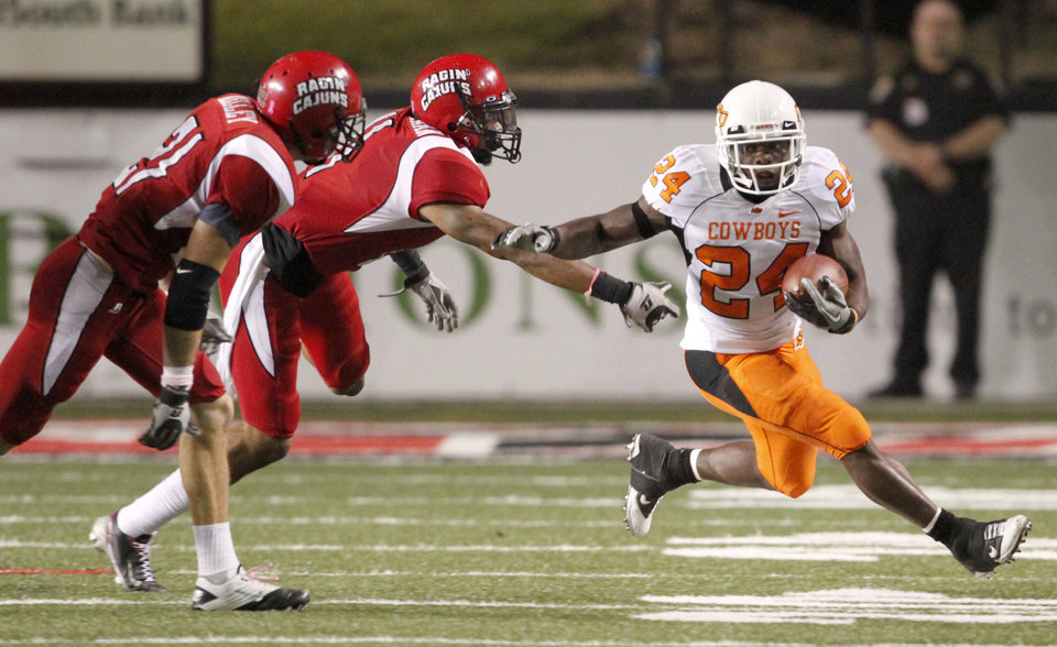 Photo - OSU's Kendall Hunter gets past  Louisiana-Lafayette's Lance Kelley, left, and Devon Lewis-Buchanan during the football game between the University of Louisiana-Lafayette and Oklahoma State University at Cajun Field in Lafayette, La., Friday, October 8, 2010. Photo by Bryan Terry, The Oklahoman