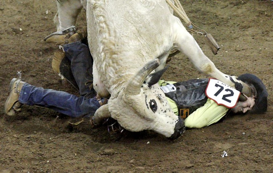 Photo -  Josh Reed gets stepped on after he hits the ground during the International Finals Rodeo at the State Fair Arena in Oklahoma City on Sunday, Jan. 16, 2011. Photo by John Clanton, The Oklahoman ORG XMIT: KOD