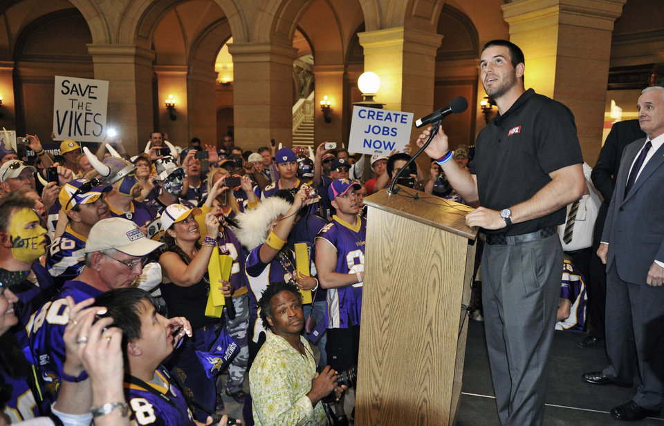 Photo -   Minnesota Vikings quarterback Christian Ponder addresses supporters during a rally in the rotunda of the State Capitol where the Minnesota House was taking up a bill for a new stadium for the a new Vikings NFL football team Monday, May 7, 2012, in St. Paul, Minn. At right is Gov. Mark Dayton. (AP Photo/Jim Mone)