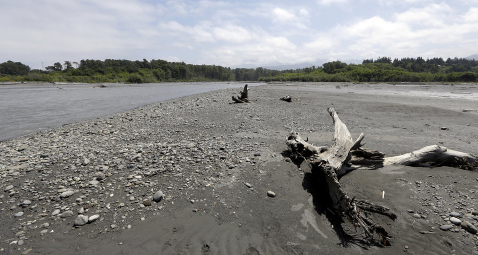 Photo - In this June 3, 2014 photo, the Elwha River flows past an extended beach at its mouth near Port Angeles, Wash. The final chunks of concrete are expected to fall this September in the nation's largest dam removal project, but nature is already reclaiming river. (AP Photo/Elaine Thompson)