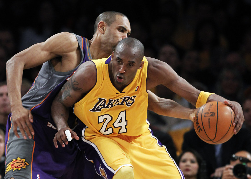 Photo - Los Angeles Lakers guard Kobe Bryant dribbles around Phoenix Suns forward Grant Hill during the second half of Game 1 of the NBA basketball Western Conference Finals on Monday. AP PHOTO