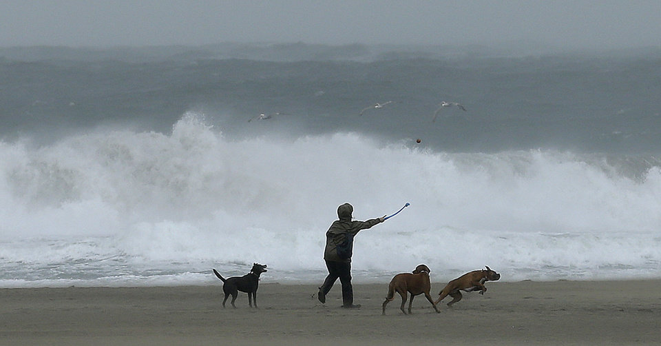 Photo - A man walks dogs amid high winds and waves during a storm hitting California Thursday, Dec. 3, 2015, at Ocean Beach in San Francisco. (AP Photo/Ben Margot)