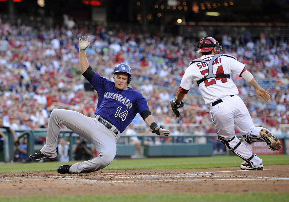 Photo - Colorado Rockies' Josh Rutledge (14) comes in to score on a single by DJ LeMahieu during the third inning of a baseball game against Washington Nationals catcher Kurt Suzuki (24), Friday, June 21, 2013, in Washington. (AP Photo/Nick Wass)