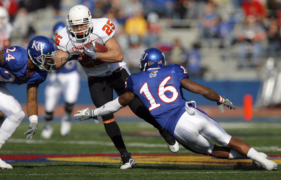 Photo - Oklahoma State's Josh Cooper (25) tries to get by Kansas' Taylor Lee (24) and Kansas' Chris Harris (16) during the college football game between Oklahoma State (OSU) and Kansas (KU), Saturday, Nov. 20, 2010 at Memorial Stadium in Lawrence, Kan. Photo by Sarah Phipps, The Oklahoman
