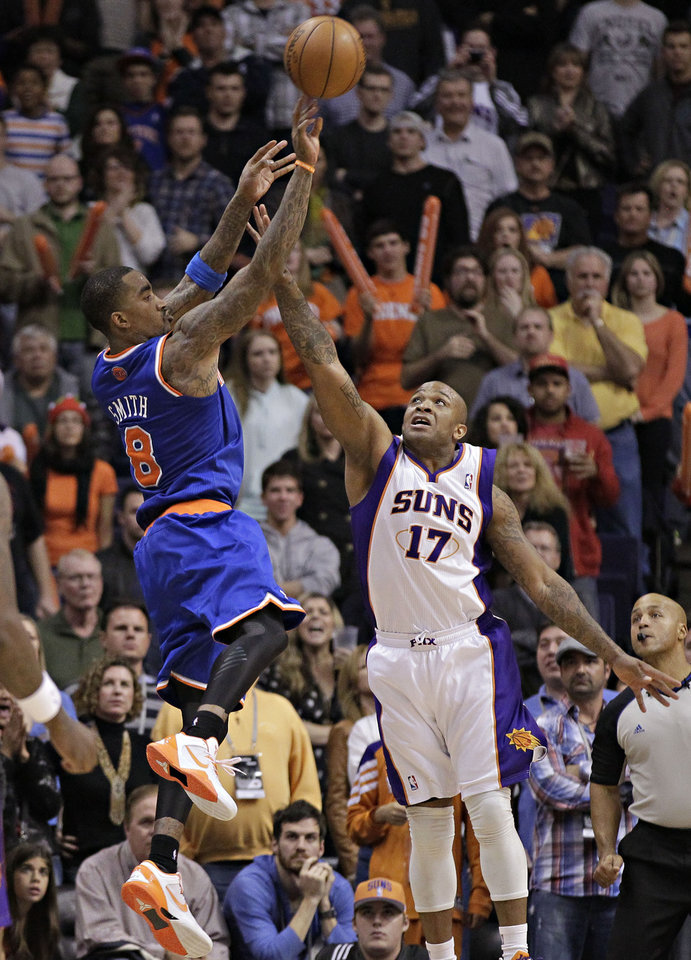 Photo - New York Knicks' J.R. Smith (9) takes the game-winning shot over Phoenix Suns' P.J. Tucker (17) during the second half of an NBA basketball game, Wednesday, Dec. 26, 2012, in Phoenix. The Knicks won 99-97. (AP Photo/Matt York)