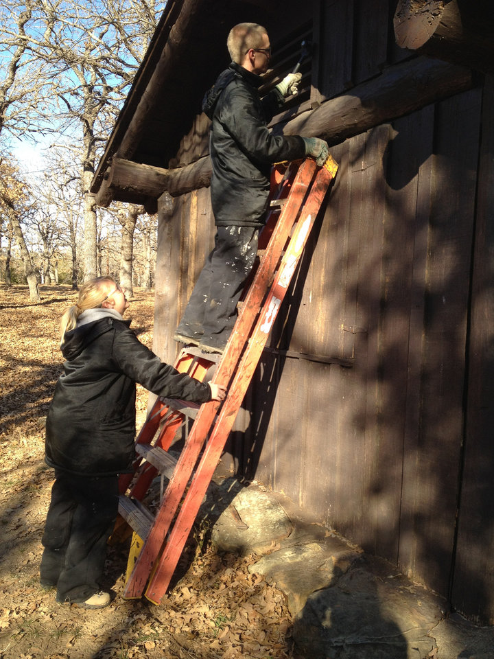 Team members Steven McKenzie and Christina Kloha scrape the exterior of a cabin at Lake Murray State Park. PHOTO BY CAROL SCHNEIDER PROVIDED.      <strong></strong>