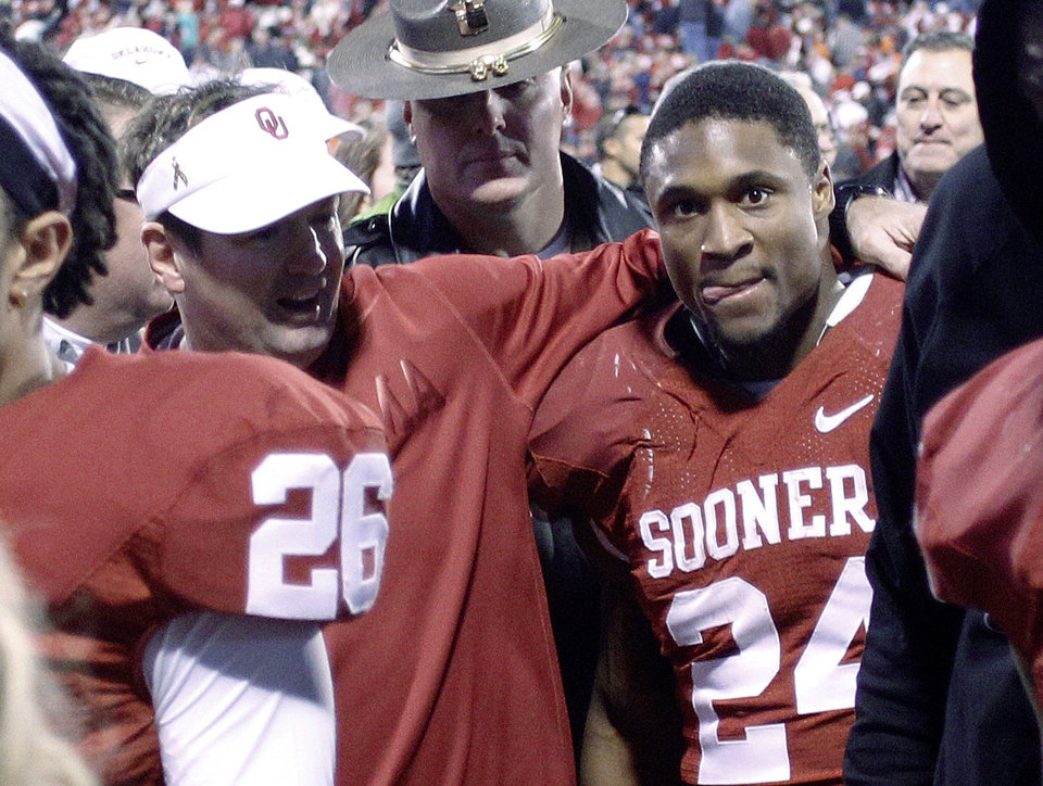Oklahoma coach Bob Stoops, left, walks off the field with running back Brennan Clay (24) after Clay scored the winning touchdown against Oklahoma State in overtime of an NCAA college football game in Norman, Okla., Saturday, Nov. 24, 2012. Oklahoma won 51-48. (AP Photo/Sue Ogrocki)