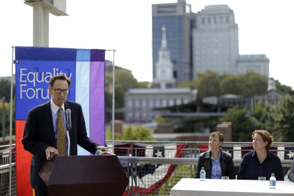 Photo - Executive Director of Equality Forum Malcolm Lazin, at podium, speaks as plaintiffs Isabelle Barker, second right, and her spouse Cara Palladino look on during a news conference, Thursday, Sept. 26, 2013, near Independence Hall in Philadelphia. Cara Palladino and Isabelle Barker, who were legally married in Massachusetts and moved to Pennsylvania, filed a federal lawsuit Thursday aiming to overturn the 1996 amendment to a state law stating same-sex marriages, including those recorded elsewhere, are not legal within the state.(AP Photo/Matt Rourke)