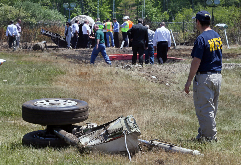 Photo - A National Transportation Safety Board official stands beside a piece of the landing gear at the scene Monday, June 2, 2014, in Bedford, Mass., where a plane plunged down an embankment and erupted in flames during a takeoff attempt at Hanscom Field on Saturday night. Lewis Katz, co-owner of The Philadelphia Inquirer, and six other people died in the crash. (AP Photo/Boston Herald, Mark Garfinkel, Pool)
