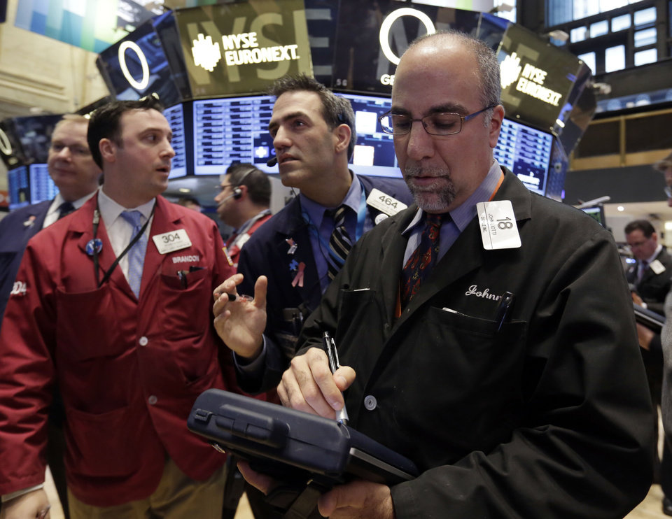 Photo - John Liotti, right, works with fellow traders on the floor of the New York Stock Exchange Thursday, Dec. 20, 2012.  Another failed attempt find a compromise in U.S. budget negotiations sent world stock markets plummeting Friday, Dec. 21, 2012 as investors feared the world's largest economy could teeter into recession if no deal is found. (AP Photo/Richard Drew)