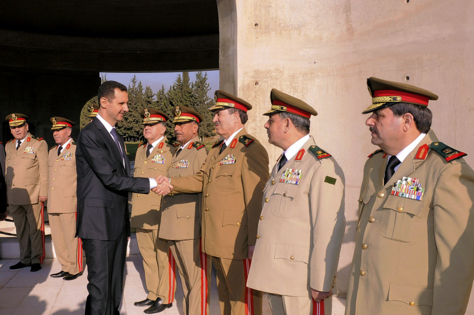 Photo -   In this photo released by the Syrian official news agency SANA, Syrian President Bashar Assad greets military officers in a ceremony marking the anniversary of the 1973 Arab-Israeli war in Damascus, Syria, Saturday, October 6, 2012. (AP Photo/SANA)